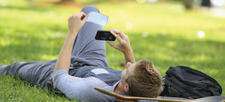 man laying in grass looking at phone